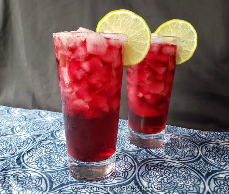 2 highball glasses with the red wine cocktail and ice garnished with lime wheels