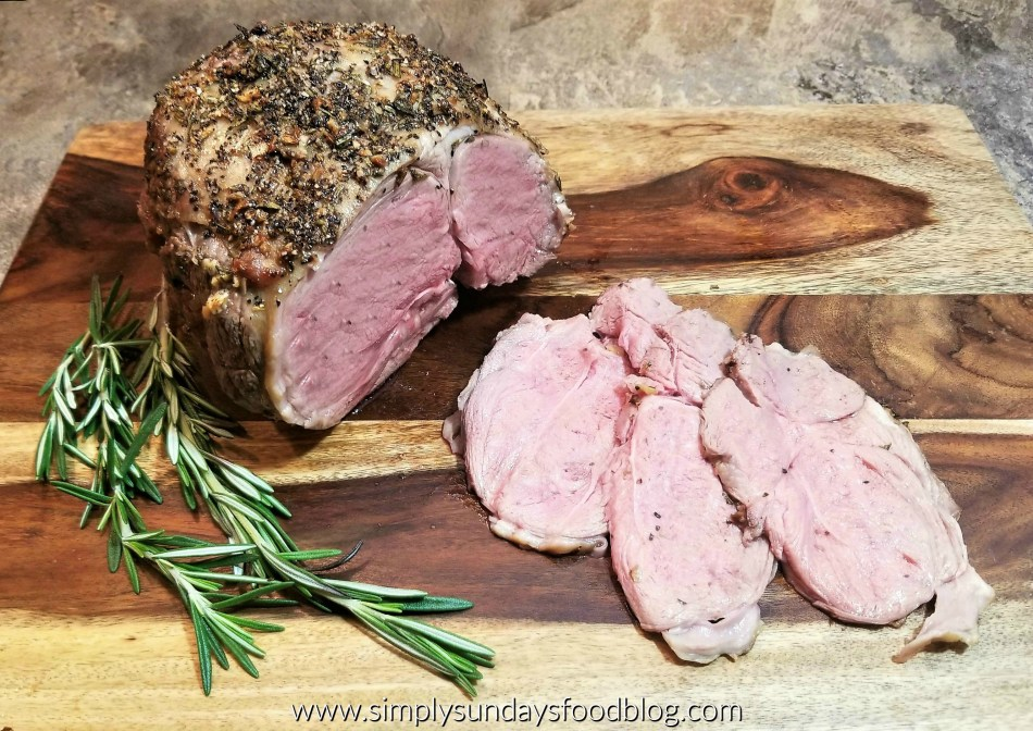 A perfectly medium cooked roast leg of lamb encrusted wit rosemary, garlic, kosher salt and ground black pepper. There are three slices fanned out in front of the roast on a dark wooden cutting board