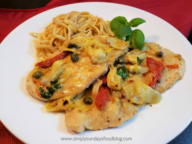 Chicken cutlets topped with bright red sundried tomatoes, artichokes, capers, fresh green basil served on a white plate