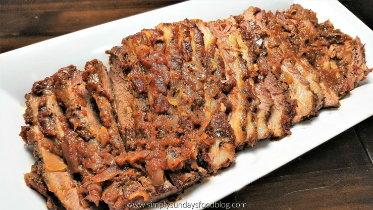 Oven roasted nicely browned brisket sliced and served with pan juices and caramelized onions in a white serving platter on a dark wood cutting board