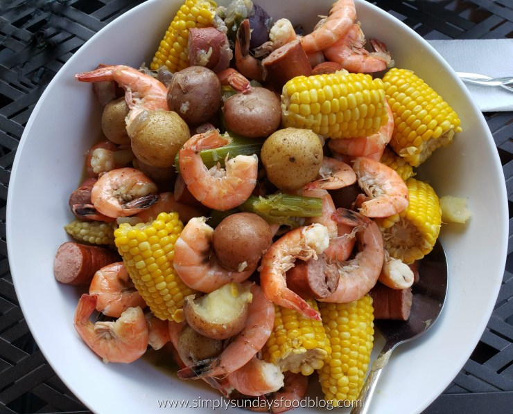 A large white bowl filled with shrimp, potatoes, corn on the cob and sausages