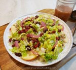 A bowl of Shaved Brussel Sprout salad with dry cranberries, sunflower seeds, pomegranate seeds and pickled red onion on a white plate on a cutting board