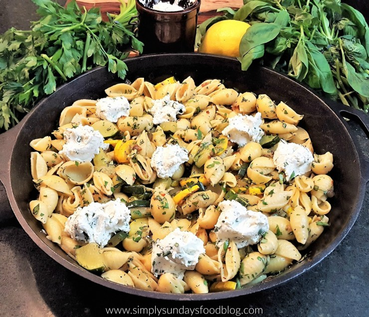 Green zucchini and yellow squash that have been caramelized tossed in pasta with lemon zest fresh herbs and creamy herbed ricotta cheese served family style in a cast iron skillet with fresh basil and parsley in the back ground