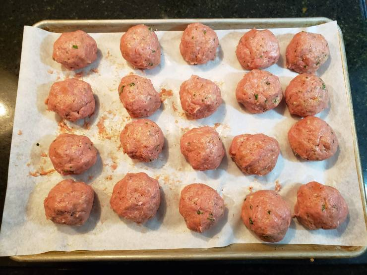 Twenty meatballs rolled out onto a parchment lined sheet pan