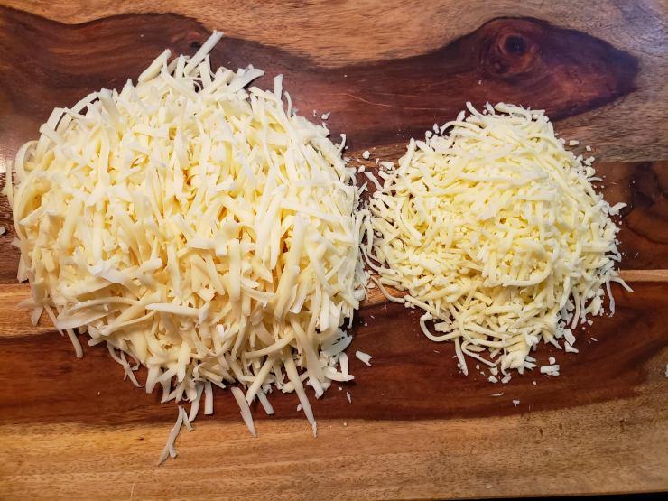 Swill, cheddar and mozzarella cheeses shredded on a cutting board