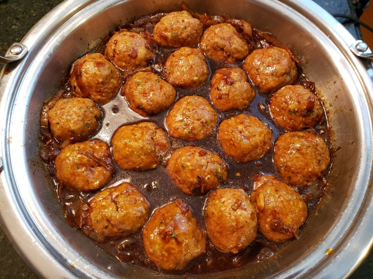 The meatballs are nestled into the pan of onion sauce