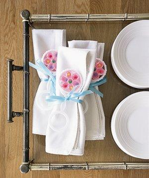 White disposable napkins are great, just tie a ribbon around and/or add a flower, or rattle and they are perfect!