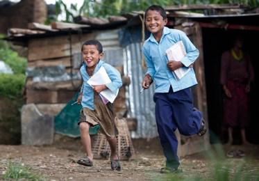 Pasang Lama, aged 6, (L) and his elder brother Mingmar Lama, aged 8, runs for school class at temporary shelter in Manedanda Talmarang village in Sindhupalchwok district , Nepal. 08 July 2015.