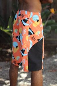 man wearing orange yellow black and teal swim trunks