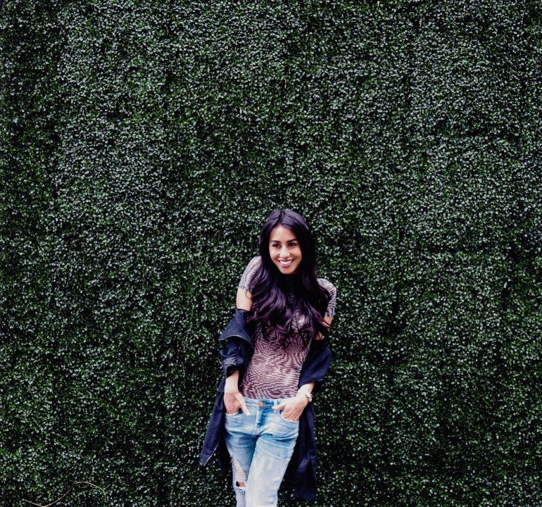 woman wearing patterned bodysuit in black and white, boyfriend jeans, and rain jacket, leaning against vine-covered wall