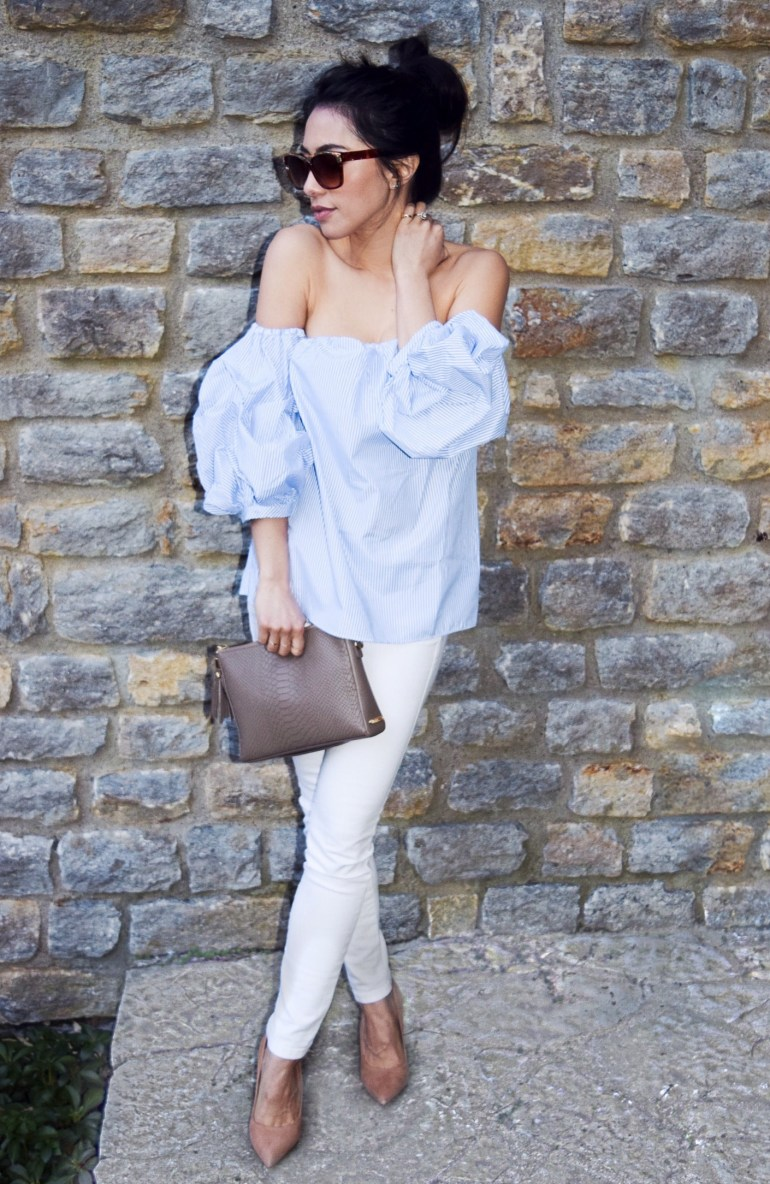 brunette blue white pinstripe off the shoulder puff sleeves white jeans light brown neutral suede block heels neutral clutch oversized sunglasses