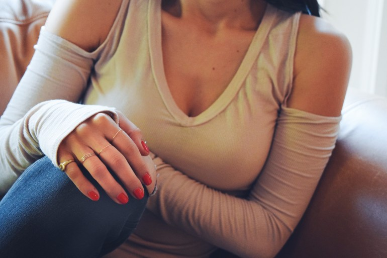 brunette wearing cold Shoulder Hazelnut Oatmeal Camel Khaki black distressed ankle jeans