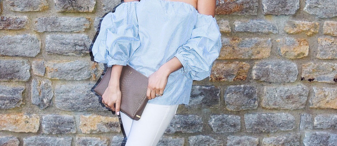 blue white pinstripe off the shoulder puffy sleeves white jeans light brown neutral suede block heels neutral clutch oversized sunglasses