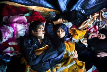 2ND PLACE SERIES- Emily Garthwaite. A pilgrim family sleep in a semi-abandoned building lit with occasional floodlights on the eve of Arbaeen in Karbala, Iraq. Surrounding the entrance and over three floors were families sleeping, swaddled in blankets. Occasionally you would find a pilgrim praying or a family sharing biscuits. The family pictured were part of a large family group - only a couple were still awake.