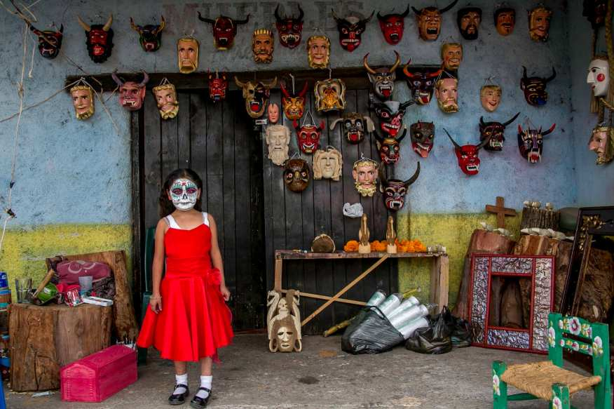 3RD PLACE SERIES- Gustavo Herera Yepez. A Purepecha girl prepares for the nights festivities in Tocuaro, a region in Michoacan, Mexico known for its intricate wood-carved masks. These masks, often representing people or animals, are used to ward off evil spirits or welcome friendly souls. The Purepecha are an indigenous group centered in the northwest region of Michoacan who continue using ancient traditions and incorporate them in their celebrations of Dia de los Muertos.