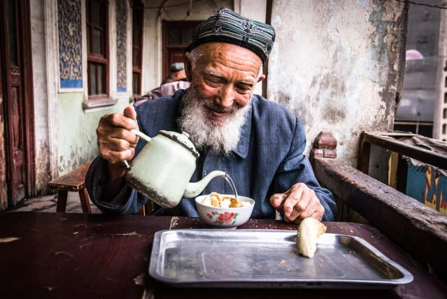 """This smiling old man is having a traditional Uighur breakfast with light green tea and a sweet bread with sesame seeds in a old tea room of Kashgar. Uighur people live in the Xinjiang Uyghur Autonomous Region, in the People's Republic of China, they are a Turkic ethnic group and they primarily practice Islam. There are many difficult contrasts between China Government and Uighur Community: Uighur people are literally fighting to preserve their identity. I was just talking with my wife last week about my trip in the Xinjiang province, in particular in the old city called Kahasgar. I would like to go there again with a better photographic experience than 6 years ago, a better equipment ( I used a Nikon d80) in order to describe better the situation of the Uyguir people, to tell their story in a better way. I would like to go there again to see what remains of the old city: probably I have had the possibility to see some old houses that also Marco Polo have seen, and now the chinese government are destroying and rebuilding the downtown, without any rules. But the worst thing is that they are trying to cancel the Uyguir traditions, costumes, language, way of life. So Uyguir language is forbidden in the schools since 2017, thousands of han ethnic people are forcibly moved by the government in Xinjiang to """"colonize"""" the area, and so on. Another Tibet, with less media resonance."""