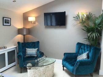 Sunroom redesign. Blue teal armchair, wall lights, Coco Deep 1955 on walls