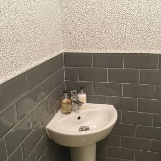 Guest bathroom redesign -with grey subway tiles and pebble style wallpaper