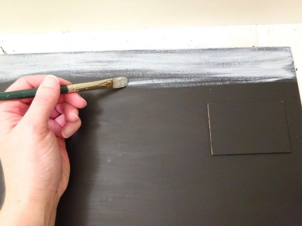painting a black sign with white paint