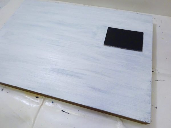 painted white sign with black square prominent