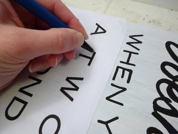tracing a template with a pen onto a sign