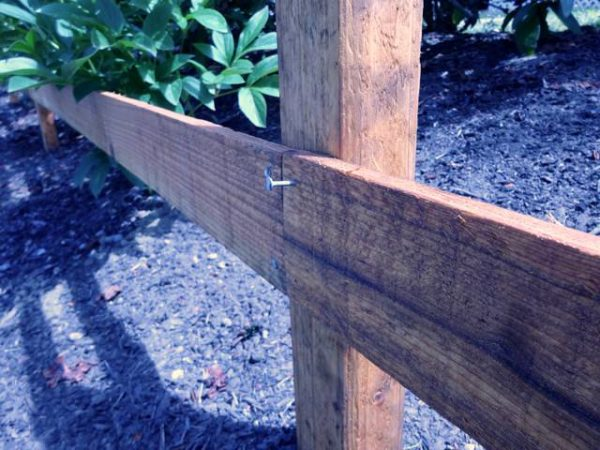 Fence rail tacked to a post with a nail