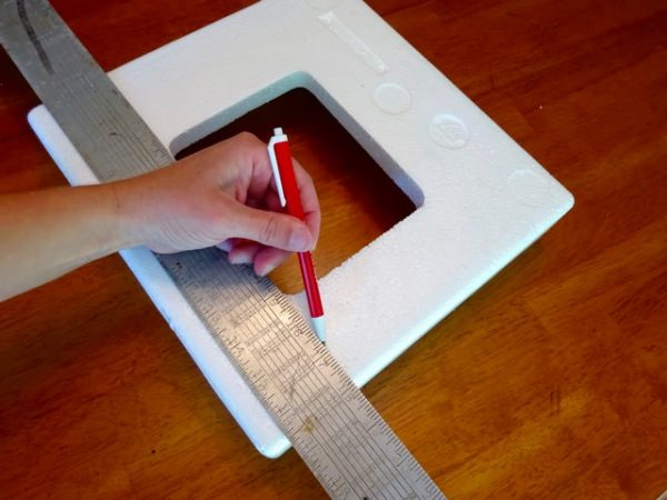 Marking a cutting line on a styrofoam block to be made into a display shelf