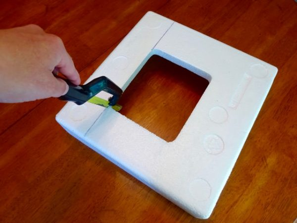 Cutting a block of styrofoam with a small hand saw