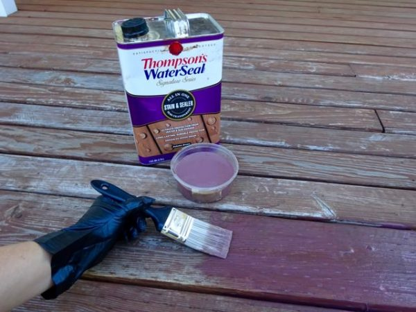 Applying deck stain to boards with a paint brush.