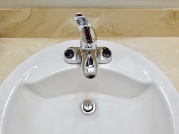Open a sink faucet to drain a hot water tank