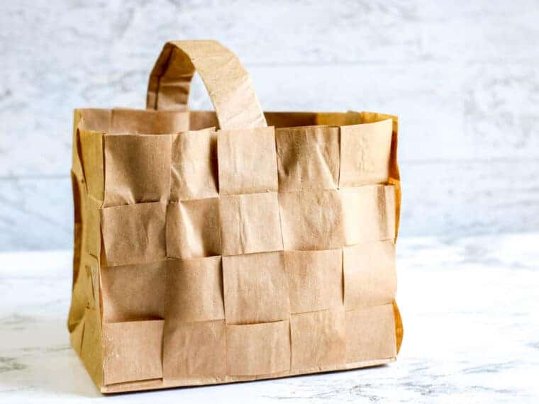 brown paper bag woven basket against marble background