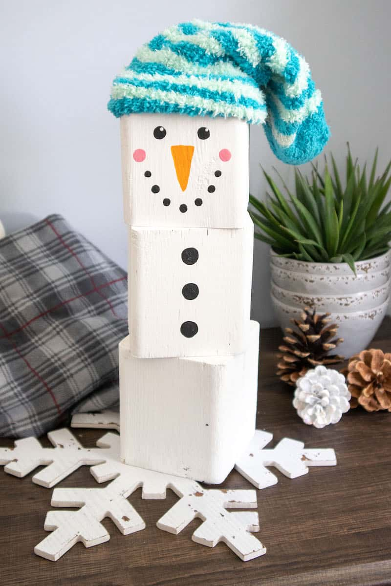 diy wood block Snowman craft with blue cap on table