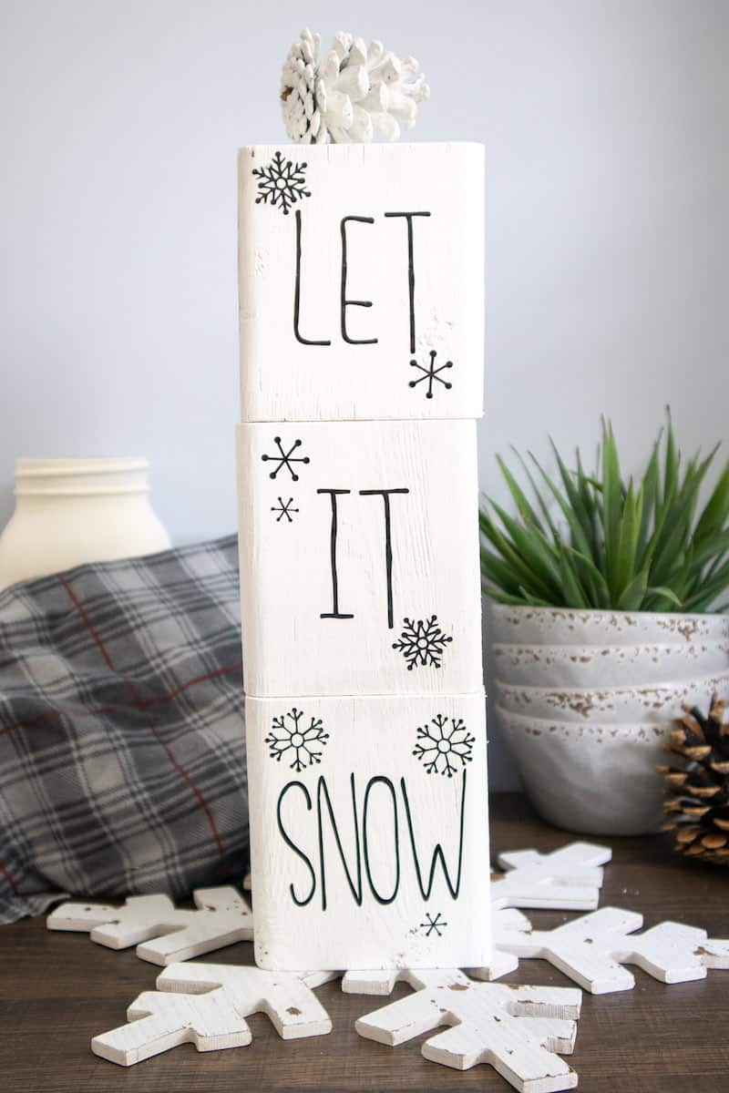 stacked painted wood block Snowman word stencils on table