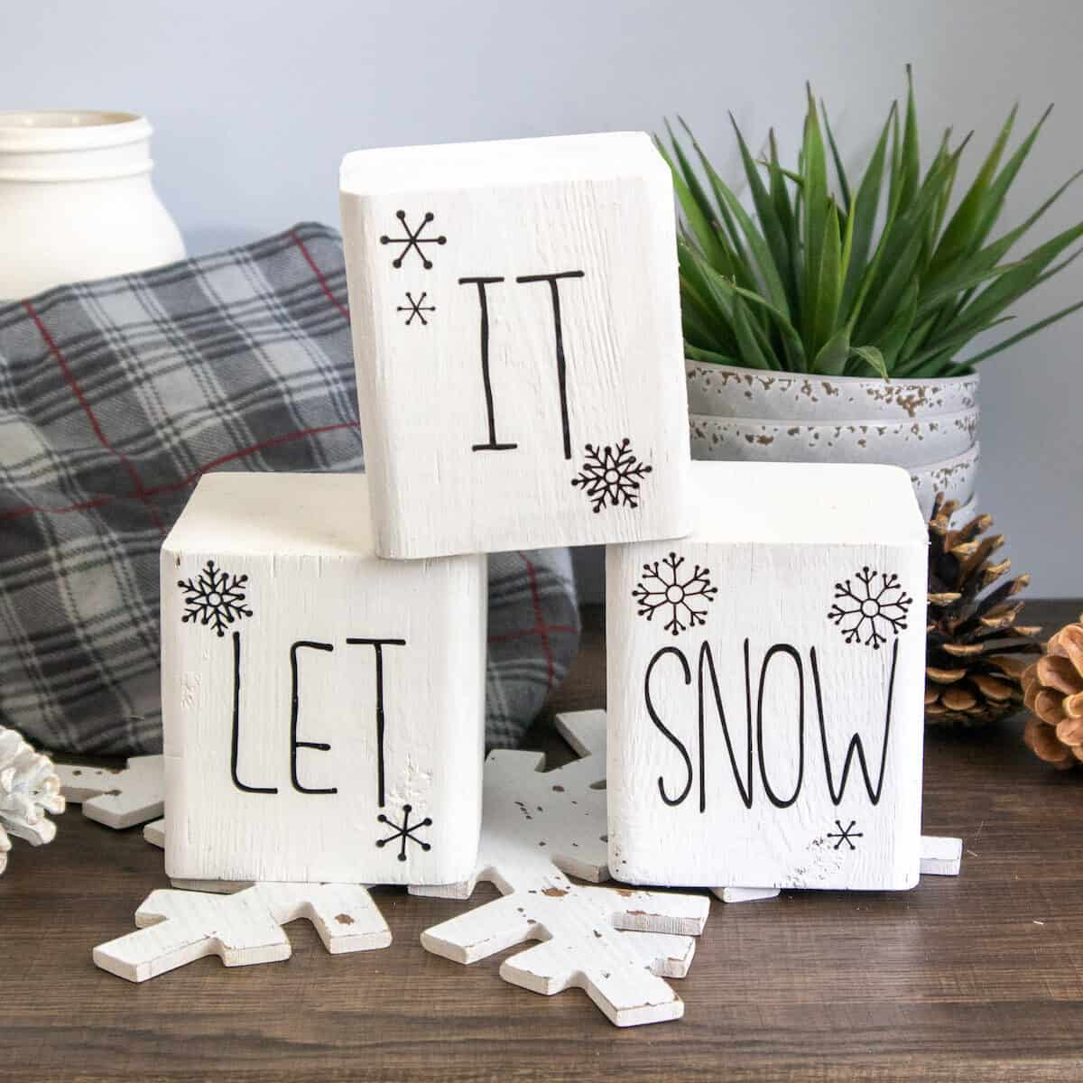 painted wood block Snowman word stencils on table