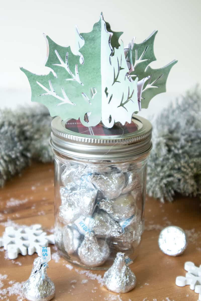 paper holly leaf holiday jar topper on mason jar filled with candy