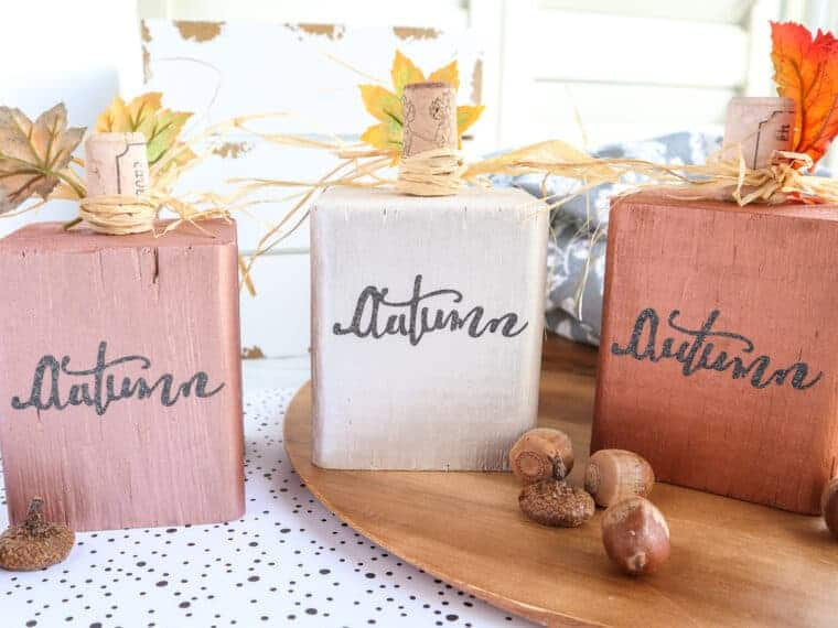 side view of metallic wood block pumpkins on table