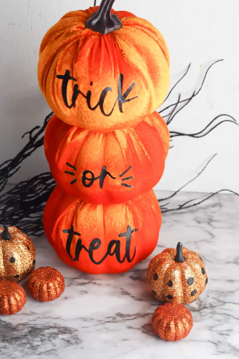 stacked dollar store pumpkins with cricut trick or treat sign