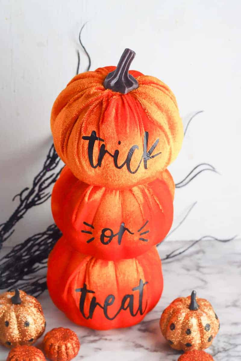 stacked dollar store pumpkins with cricut vinyl letters