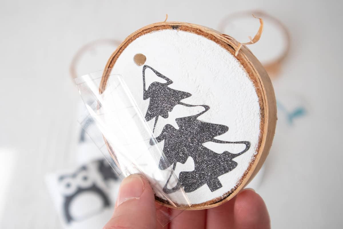 peeling away cricut transfer tape from vinyl on wood slice ornament