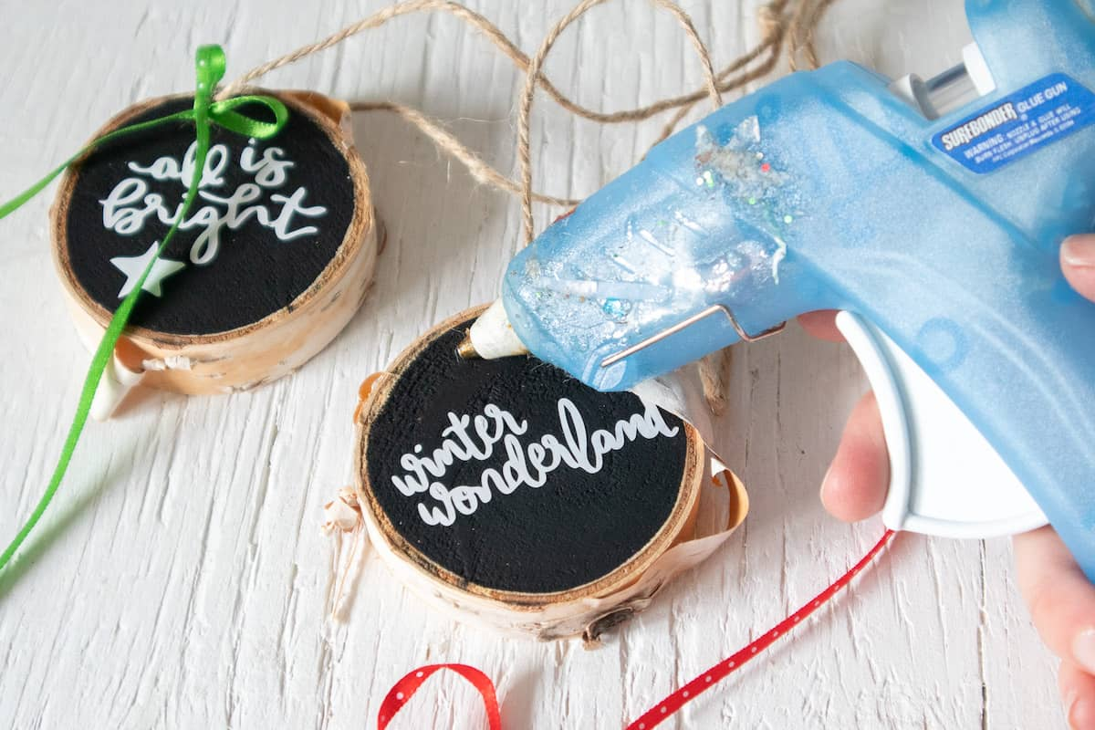 glue gun and lettered wood slice ornaments