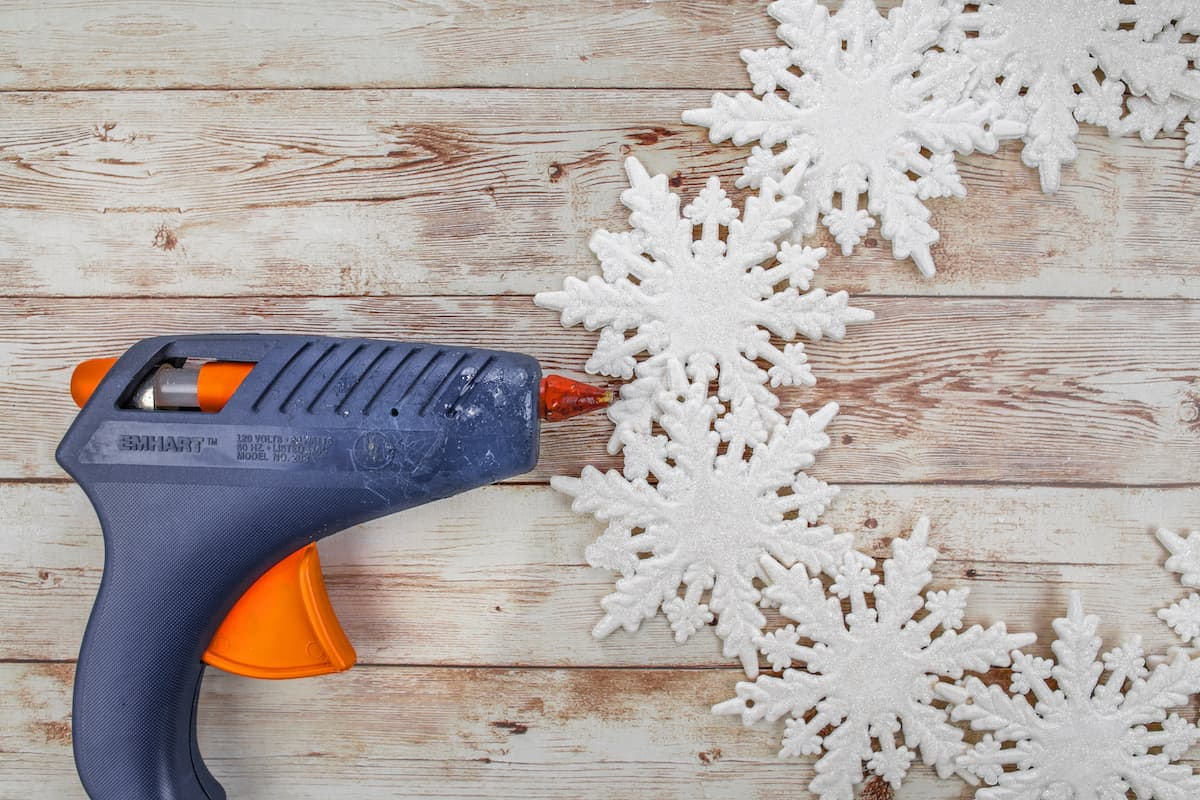 hot glue gun and snowflake ornaments on wooden table