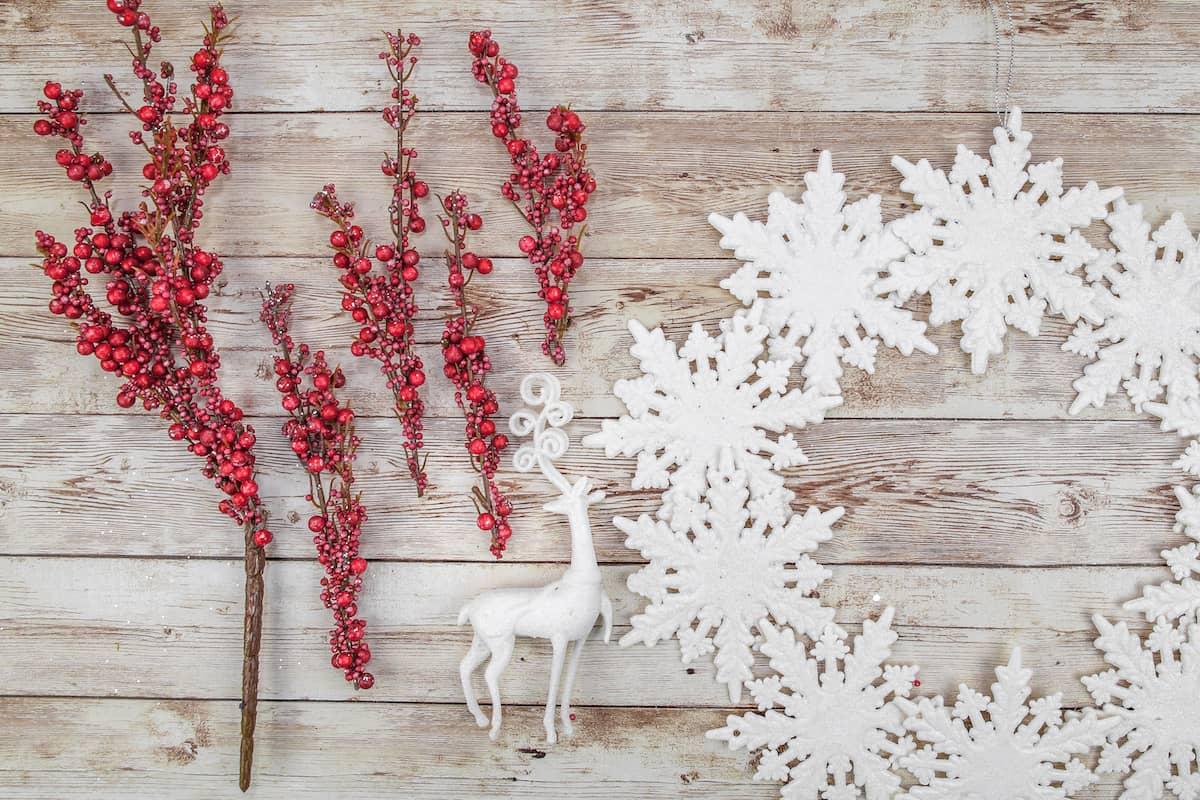 red berry picks next to snowflake wreath