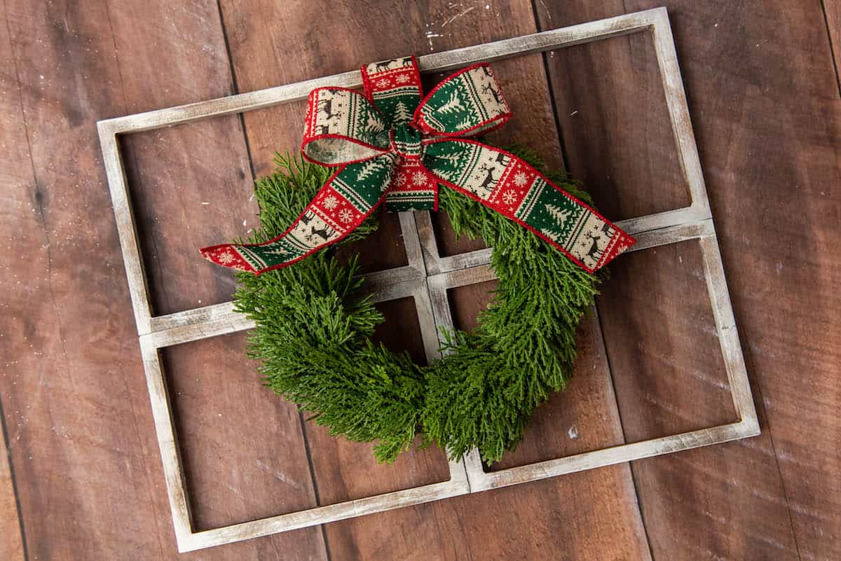 Christmas wreath with bow on a faux window