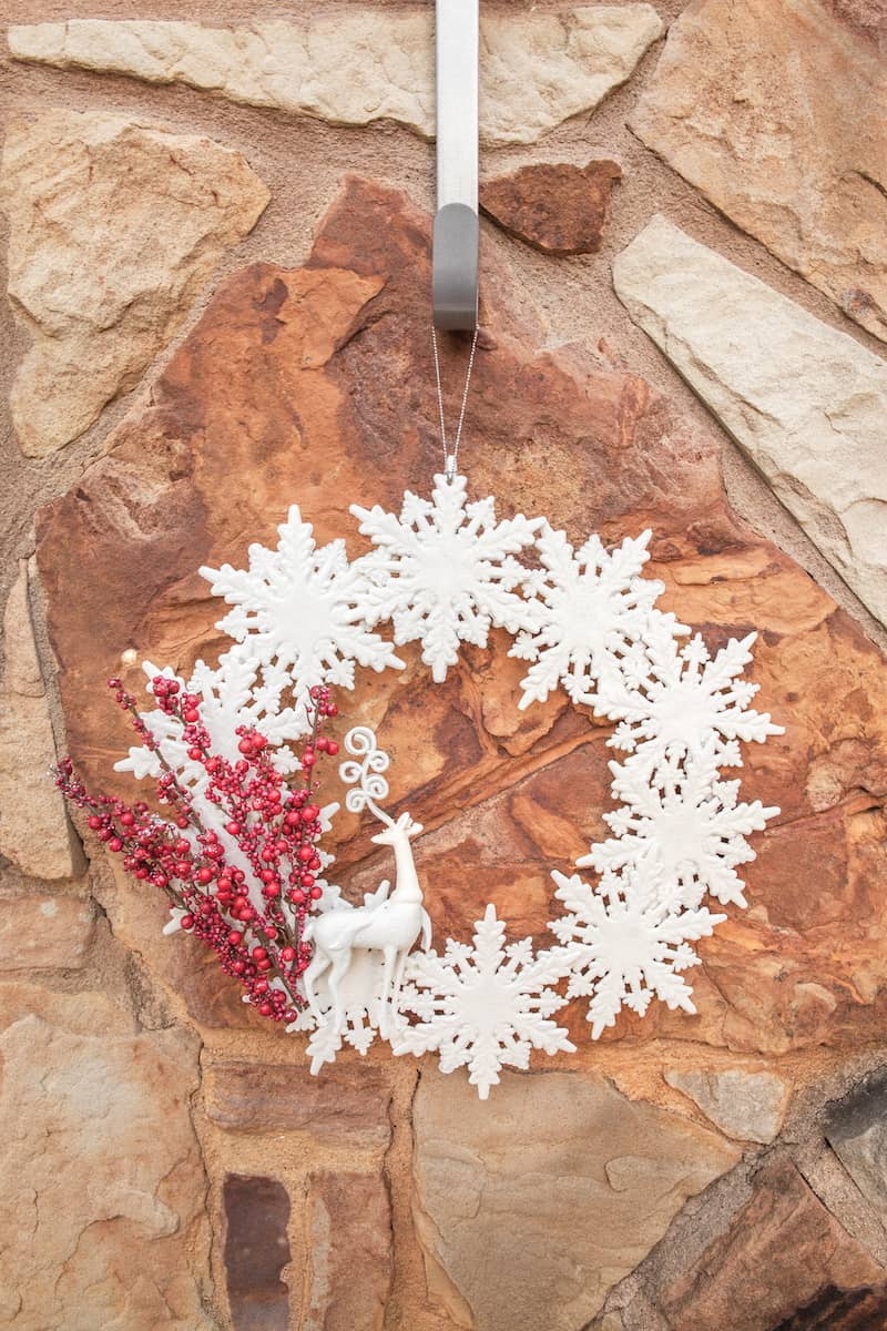 snowflake and deer wreath hanging on a rock wall