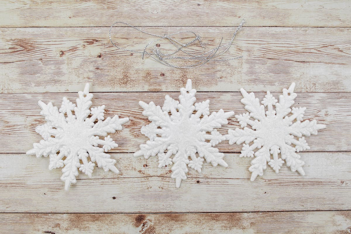 three white snowflake ornaments on wooden background