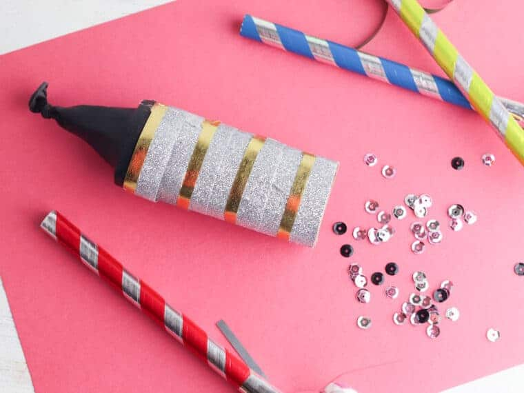 doy confetti cannon on pink background with sequins nearby