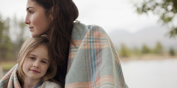 Portrait of smiling daughter wrapped in blanket with mother at lakeside