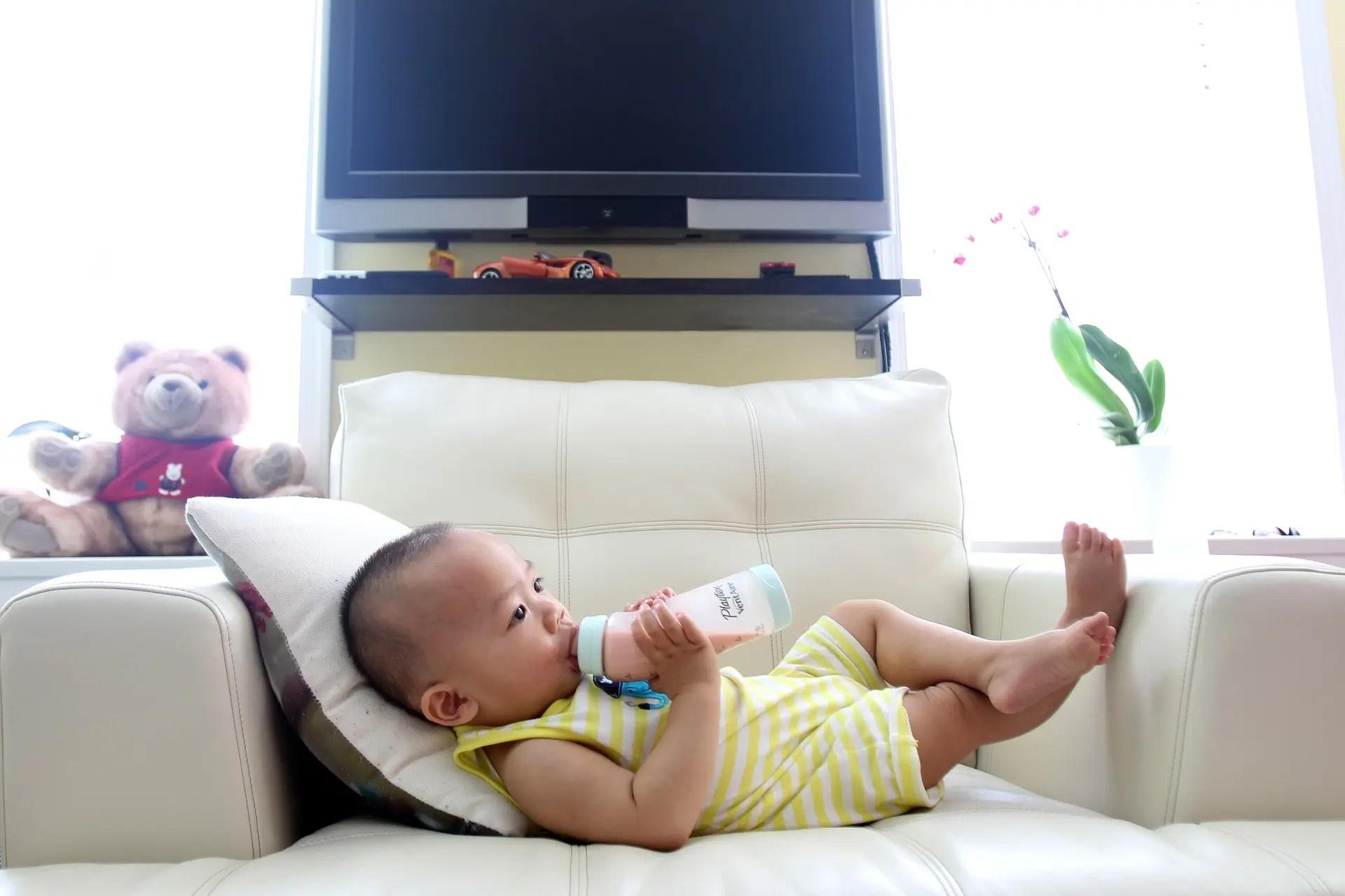 Baby drinking milk on a sofa