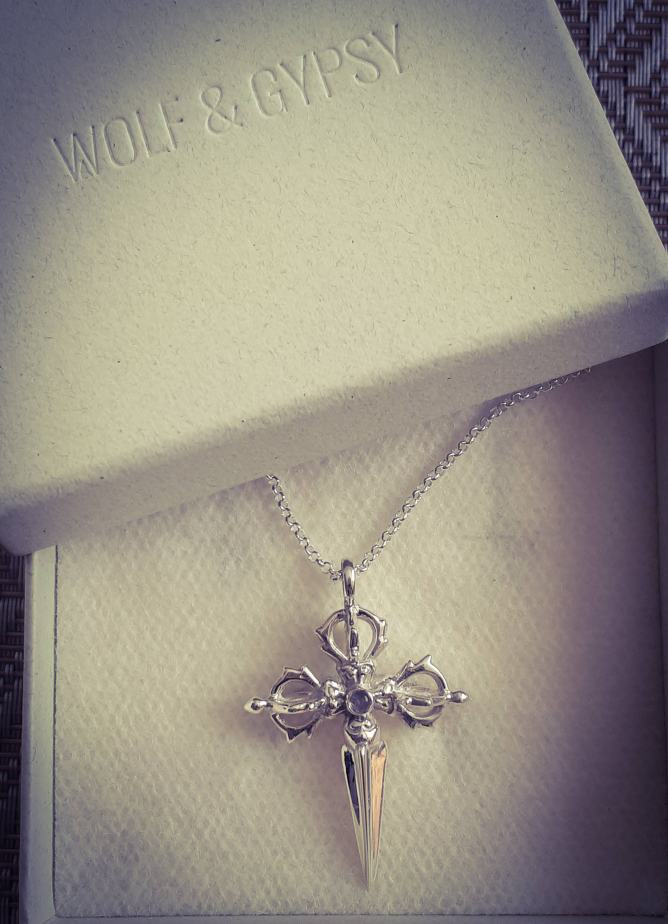 The Moonstone Tibetan Cross Necklace laid in its box with the lid above it, showing the logo.
