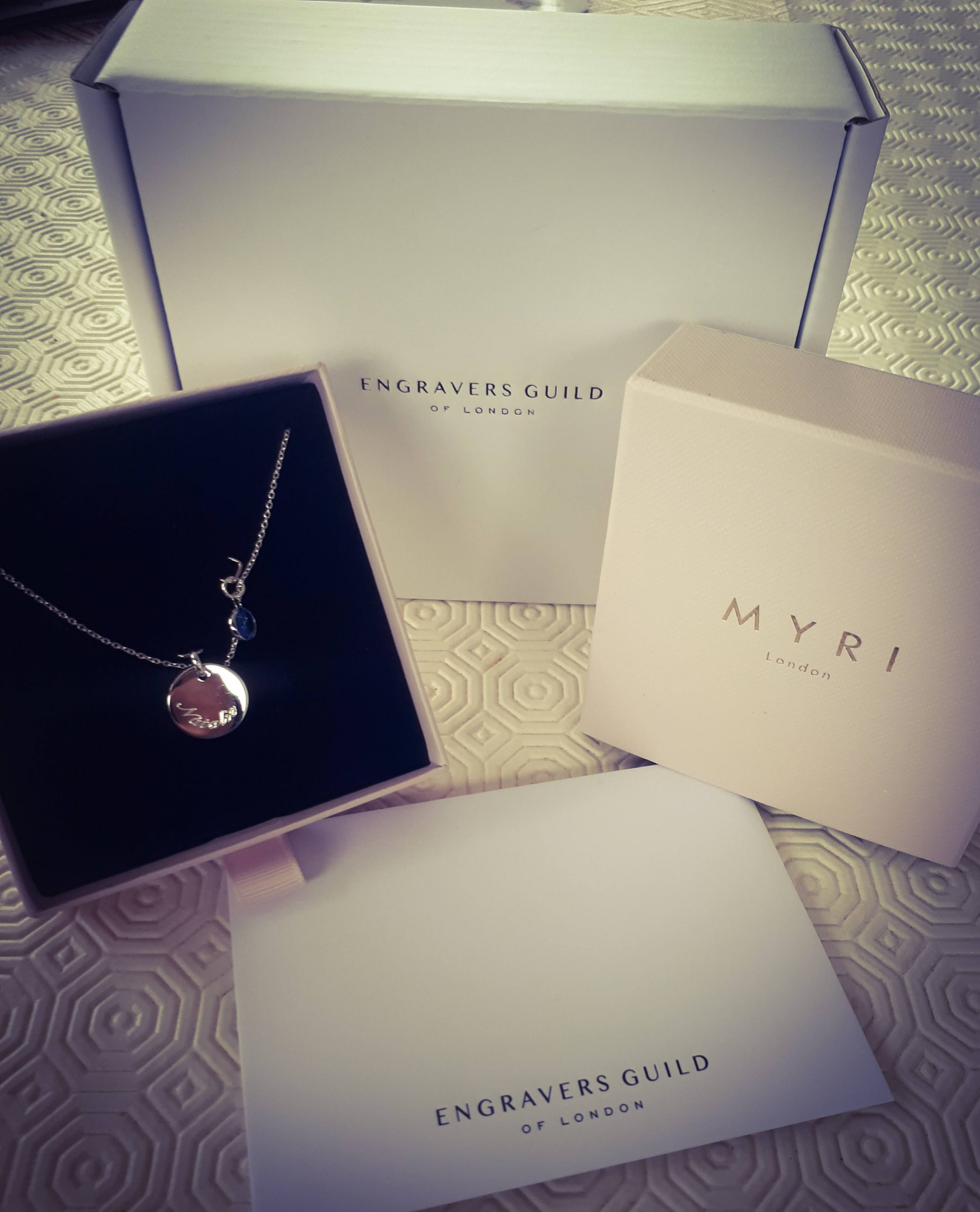 Necklace displayed in its box in front of the packaging